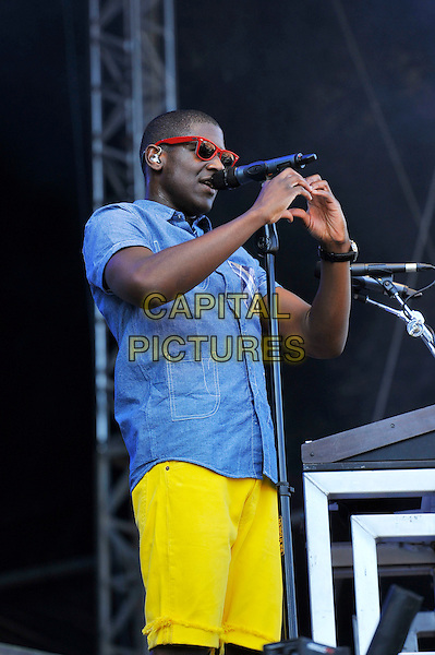 Labrinth (Timothy McKenzie).performing at V Festival, Hylands Park, Chelmsford, Essex, England. .18th August 2012.on stage in concert live gig performance music half length blue shirt yellow shorts sunglasses shades singing side hands arms heart shape   .CAP/MAR.© Martin Harris/Capital Pictures.