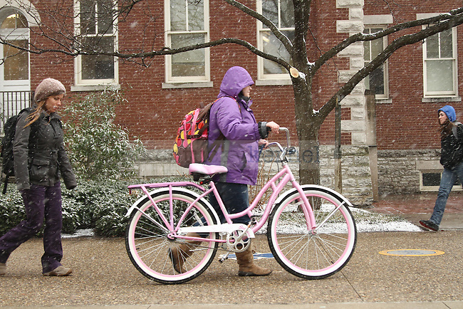 Elementary education junior Alyssa Howell walks her pink bike through campus during the beginning of Thursday's snow storm. Photo by Brandon Goodwin | Staff