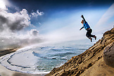 Cannon Beach USA, Oregon, Pacific City, a a young boy jumps off a sand dune at Pacific City Beach