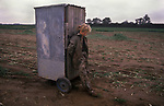 Rural low paid part time farm work the Fens, East Anglia. 1980s UK. This is the toilet cabin, her friend is inside and she is guarding the door.