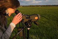 Rita Norvaisaite, from the Baltic Environmental Forum, checks the telescope while leading a birdwatching group during a bird festival in the Nemunas River Delta, LithuaniaNemunas River Delta, Lithuania