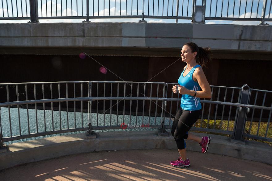Female runner running cardio workout on the stairs, Lamar Pedestrian Bridge in downtown Austin, Texas.