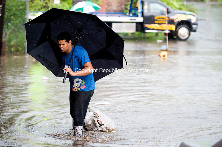 WATERBURY, CT-063017JS08- Zack Oquendo clears debris from the drainage grates after heavy rains flooded the intersection of South Main Street and Washington Avenue in Waterbury on Friday. <br /> Jim Shannon Republican-American