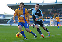 Mansfield Town's Lee Collins under pressure from Wycombe Wanderers Garry Thompson during the Sky Bet League 2 match between Mansfield Town and Wycombe Wanderers at the One Call Stadium, Mansfield, England on 31 October 2015. Photo by Garry Griffiths.