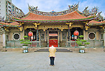 A lone worshipper stands in front of Longshan Temple as he prepares to enter and worship.