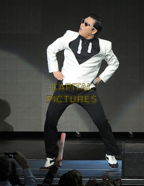 Psy (Park Jae sang).KIIS FM Jingle Ball Night 2 held at Nokia Live in Los Angeles, California, USA..3rd December 2012 .on stage in concert music gig performing live performance full length white sunglasses shades black jacket suit trousers hands on hip profile dancing  .CAP/DVS.©DVS/Capital Pictures.