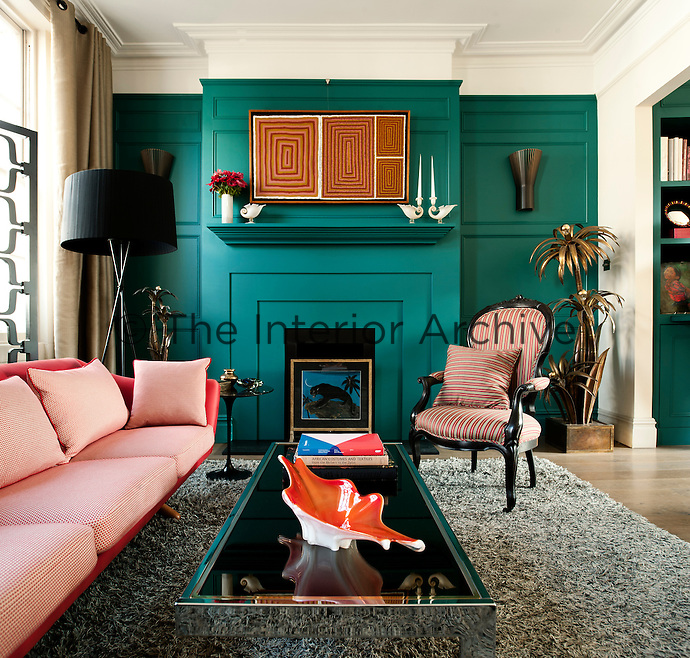 In the living room the painted wooden panelling was inspired by the Georgian period and painted in a teal colour by the Paint and Paper Library. The 1960s Danish sofa was given a fresh appearance with with fabric by New Zealand based Mokum and the late 19th century chair is covered with stripy fabric by Donghia. The beautifully eccentric brass palm lights are by Maison Jansen.