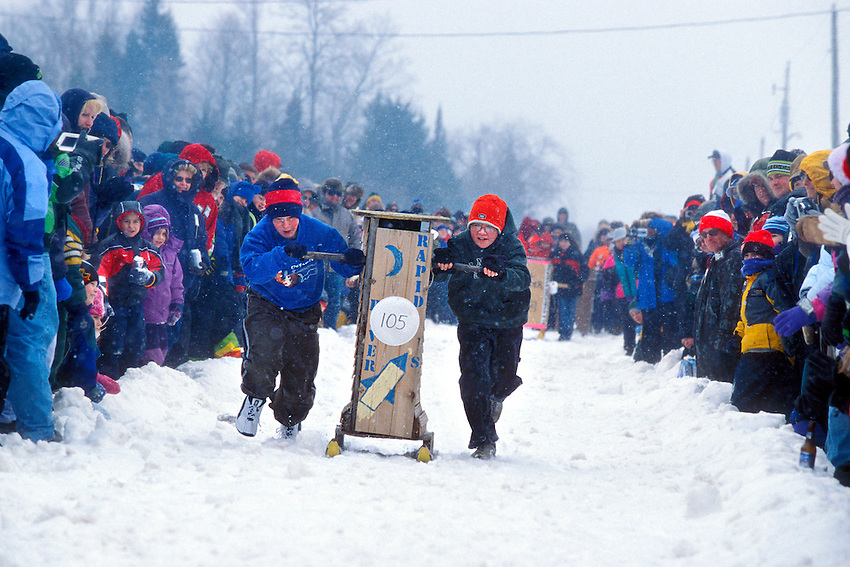Young people push outhouses down a snowy runway in downtown Trenary Michigan during the Outhouse Classic outhouse racing festival in February.