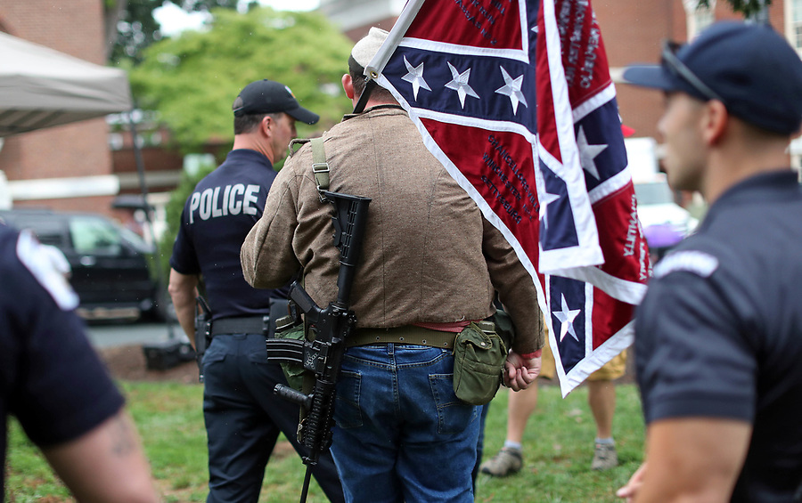 Charlottesville police escort Allen Armentrout of North Carolina out of Emancipation Park after Charlottesville residents confronted him Tuesday, Aug. 15, 2017 at Emancipation Park in Charlottesville, Va. Armentrout wore a Confederate outfit with 2 guns as he stood protecting the Lee Statue. Photo/Andrew Shurtleff