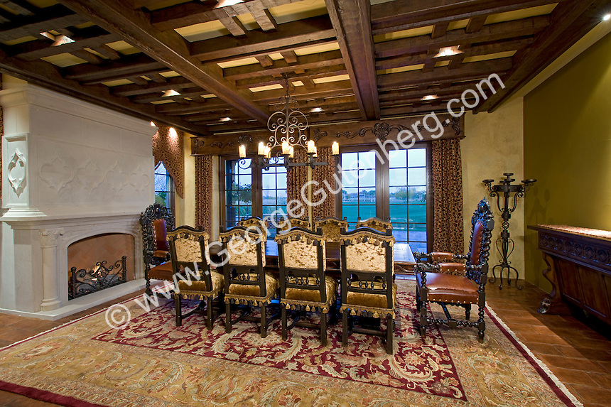 Luxurious Dining room with coffered ceiling and white stone fireplace set against large paned windows Stock photo of residential dining room