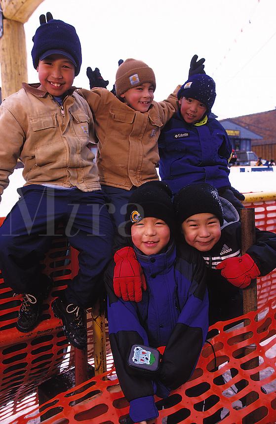 Native Alaskan children gather in a smiling, playful group. Alaska.