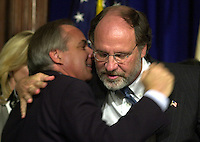 U.S. Senator Robert Torricelli (L), is embraced by U.S. Senator Jon Corzine (R), after Torricelli announced he is dropping out of the US Senate race, Monday, Sept. 30, 2002, in Trenton, New Jersey. (Photo by William Thomas Cain)