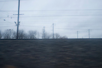 View of Train Tracks and Electric Power Lines along the  Northeast Corridor/New Jersey Transit railroad tracks in Central New Jersey, on an overcast afternoon, blurred motion.....Central New Jersey, USA
