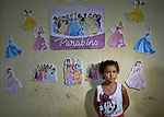 Deborah, age 5, poses in front of film characters she has posted on the wall of a small room she shares with her family in a building in Manaus, Brazil. The Kokama indigenous family migrated to the city in 2018, but unable to find decent housing they could afford, they joined with other poor families to take over an unoccupied building--the Casa do Estudante--in the city center. Caritas, a ministry of the Catholic Church, has helped the families in their struggle.<br /> <br /> Written parental consent obtained.