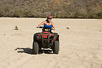 Woman riding a Quad in the arroyo near Migrino, Baja California, Mexico