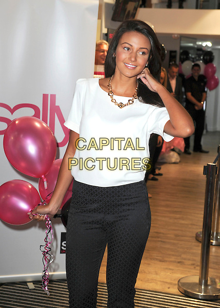 Michelle Keegan <br /> attends a photocall to launch the new 'Sally' store on Oxford Street, London, England, UK, September 12th 2013.<br /> half length shop white top black trousers holding pink balloons <br /> CAP/PP/GM<br /> &copy;Gary Mitchell/PP/Capital Pictures