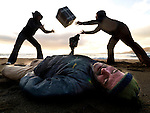 25-11-08: 'Cocaine on beach in West Kerry': A man lies dead in the sand as locals grab 'crack cocaine' on Comeenole strand in West Kerry in a scene from the Irish play 'Raic' by the AnnOg Theatre group which will open the new Irish language theatre for Corca Dhuibhne, called Lab na Mainistreach in Dingle at the weekend. Actors, Malachai MacAmhlaoibh, Mathew Sean O'Grifin, Liam Antaine o'Cathasaigh and Antonio Fazio Top in a cast of 10 will be on hand as Irish comedian and 'gaelgoir' Des Bishop perfoms the opening on Saturday night. The play centres on  brandy smuggling in the 19th Century and on the smuggling of crack cocaine today.<br /> Picture by Don MacMonagle<br /> <br /> Story by Anne Lucey