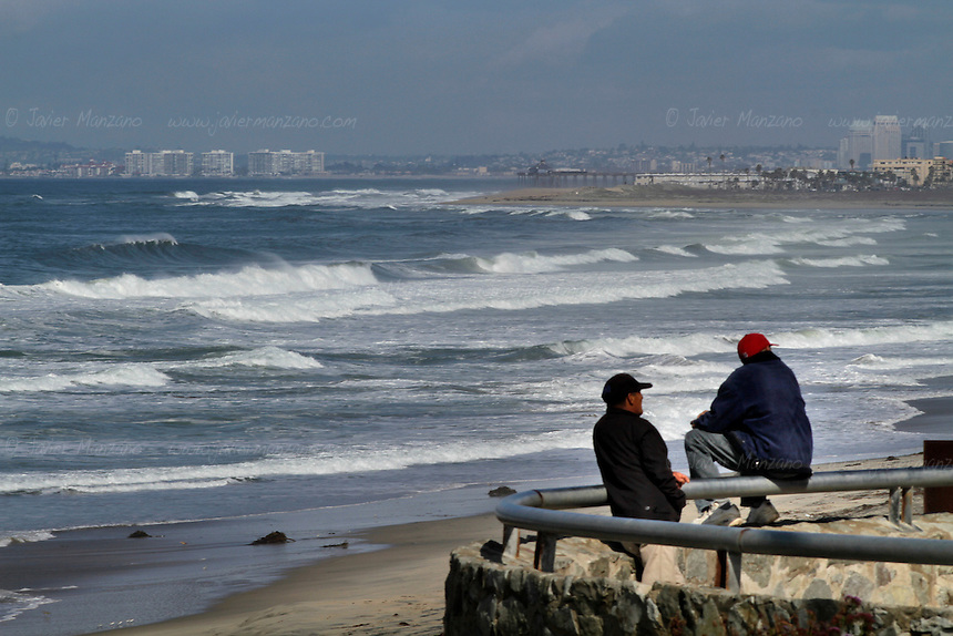 Local residents relax by the fence that separates the United States from the border city of Tijuana, Baja California, Mexico on February 9, 2013.  The city of San Diego is seen in the distance - heavy surveillance has made it virtually impossible for undocumented immigrants to enter the United States through this section of the border.  (Javier Manzano / For The Washington Post).