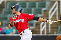 Kannapolis Intimidators third baseman Nick Basto (27) follows through on his swing against the Greensboro Grasshoppers at CMC-Northeast Stadium on July 13, 2013 in Kannapolis, North Carolina.  The Intimidators wore throwback jerseys of the Piedmont Boll Weevils, who played in Kannapolis from 1996-2000.   (Brian Westerholt/Four Seam Images)