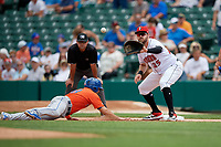 Indianapolis Indians first baseman Will Craig (25) waits for a pickoff attempt throw as Danny Espinosa (18) dives back to the bag with umpire Jeremy Riggs looking on during an International League game against the Syracuse Mets on July 17, 2019 at Victory Field in Indianapolis, Indiana.  Syracuse defeated Indianapolis 15-5  (Mike Janes/Four Seam Images)
