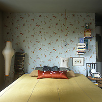 A bedroom with blue floral pattern wallpaper. The room is furnished with a double bed with a yellow cover and a retro floor lamp stands to one side.