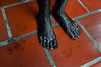 Feet of Diana R., who claims to be possessed by spirits, seen covered by black mud before a ritual of exorcism performed by Hermes Cifuentes in La Cumbre, Colombia, 28 May 2012. Exorcism is an ancient religious practice of evicting spirits, generally called demons or evil. Although the formal catholic rite of exorcism is rarely seen and must be only conducted by a designated priest, there are many pastors and preachers in Latin America performing exorcism ceremonies. The 52-year-old Brother Hermes, as the exorcist calls himself, claims to have been carrying out the healing rituals for more than 20 years. Using fire, dirt, candles, flowers, eggs and other natural-based items, in conjunction with Christian religous formulas, he attempts to drive the supposed evil spirit out of a victim's mind and body.