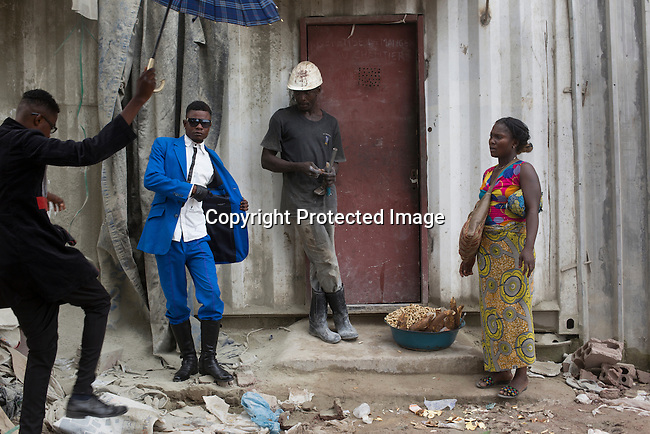 """KINSHASA, DEMOCRATIC REPUBLIC OF CONGO - FEBRUARY 10: Young Sapeurs parade and show their designer label clothes while paying their respect to Stervos Nyarcos, the founder of the .kitendi religion., which means clothing in local language Lingala. Nyarcos was known as the leader of the Sape movement, at Gombe cemetery on February 10, 2016 in Kinshasa, DRC. The word Sapeur comes from SAPE, a French acronym for Société des Ambianceurs et Persons Élégants. or .Society of Revellers and Elegant People. and it also means, .to dress with elegance and style"""". Most of the young Sapeurs are unemployed, poor and live in harsh conditions in Kinshasa,  a city of about 10 million people. For many of them being a Sapeur means they can escape their daily struggles and dress like fashionable Europeans. Many hustle to build up their expensive collections. Most Sapeurs could never afford to visit Paris, and usually relatives send or bring clothes back to Kinshasa. (Photo by Per-Anders Pettersson)"""