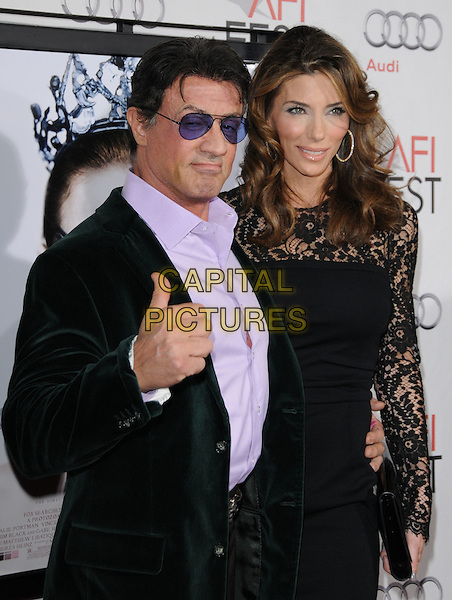 "SYLVESTER STALLONE & JENNIFER FLAVIN.The AFI Fest 2010 Closing Night Gala - ""Black Swan"" Premiere held at The Grauman's Chinese Theatre in Hollywood, California, USA .November 11th, 2010       .half length purple black sunglasses shades shirt suit jacket black lace hand thumb up married husband wife green velvet.CAP/RKE/DVS.©DVS/RockinExposures/Capital Pictures."