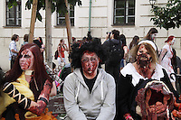 2 women and a man sitting on a bench, dressed up for the Zombie Walk in Prague, Europe in May 2014.
