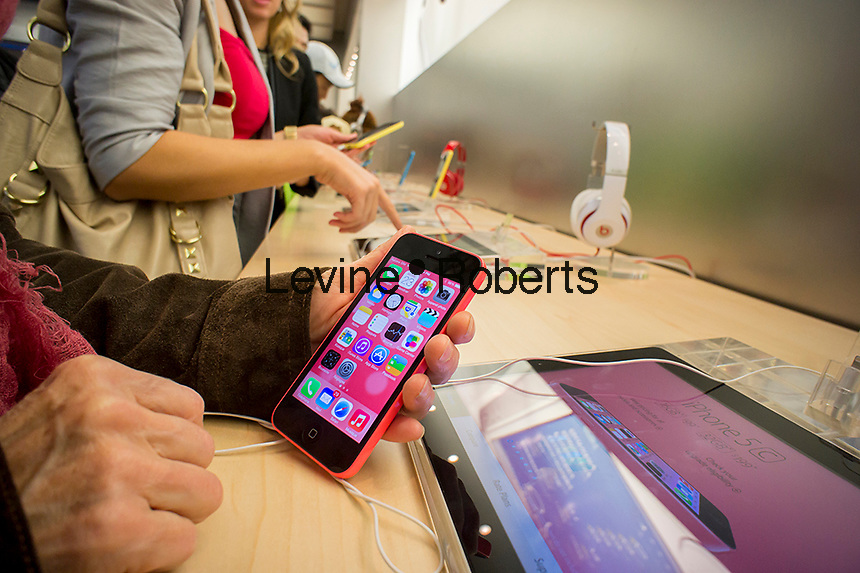 A consumer tries a new iPhone 5C in an Apple store on Fifth Avenue in New York on Monday, September 23, 2013.  This iteration of the iPhone 5 went on sale on Friday, September 20 and sales topped 9 million units over its inaugural weekend. Over 200 million people have downloaded and updated to the new iOS7 so far also.(© Richard B. Levine)