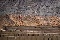 A Peruvian boy climbs the heap of mud while working at a brick factory in Huachipa, a suburb in the outskirts of Lima, Peru, 10 August 2012. Child labour is a common practice at the artisanal brick factories, found predominantly in socially deprived areas of the urban zones. Poverty and lack of employment force parents, mainly season workers coming from rural areas of the country, to employ their own children, in an effort to ensure the livelihood for the whole family. Children aged 4-7 take part in simple jobs while children aged 8 and up tend to work regularly, same as adults. A family group, consisting of 2 adults and 2-3 children, may earn 20-25 USD per day, working almost the whole day, often in harsh climatic conditions.