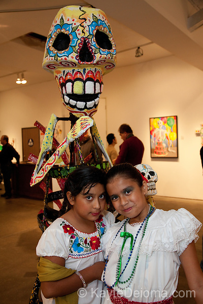 Two Mexican girls pose with a calaca skeleton sculpture at the Dia de Los Muertos (Day of the Dead) celebration at an art gallery in Long Beach, CA