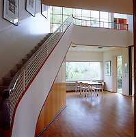 The curved staircase sweeps gracefully from the entrance hall to an upper gallery