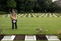 A Japanese man wearing a poppy looks at the graves of fallen servicemen and service women during t he Remembrance Sunday ceremony at the Hodogaya, Commonwealth War Graves Cemetery in Hodogaya, Yokohama, Kanagawa, Japan. Sunday November 11th 2018. The Hodagaya Cemetery holds the remains of more than 1500 servicemen and women, from the Commonwealth but also from Holland and the United States, who died as prisoners of war or during the Allied occupation of Japan. Each year officials from the British and Commonwealth embassies, the British Legion and the British Chamber of Commerce honour the dead at a ceremony in this beautiful cemetery. The year 2018 marks the centenary of the end of the First World War in 1918.