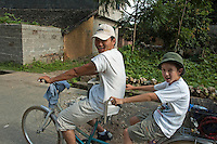 Chinese man riding tandem with a young boy in Yangshuo, Guangxi, China.