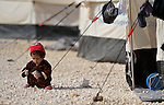 A small child plays with rocks in the Zaatari Refugee Camp, located near Mafraq, Jordan. Opened in July, 2012, the camp holds upwards of 50,000 refugees from the civil war inside Syria. International Orthodox Christian Charities and other members of the ACT Alliance are active in the camp providing essential items and services.