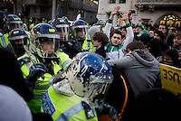 Police that have been hit by paint bombs clash with protestors during a student demonstration in Westminster, central London on the day the government passed a bill to increase university tuition fees.