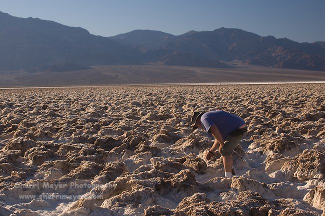 Man examining the salt at the Devil's Golf Course, Death Valley National Park, California