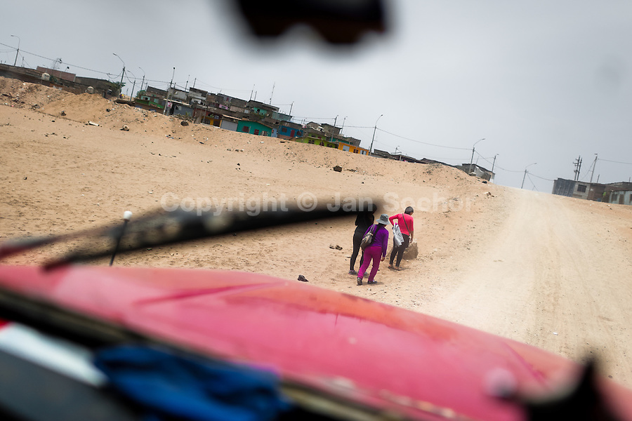 Peruvian women, climbing up a sandy path, are seen from a cabine of a water truck distributing drinking water on the dusty hillside of Pachacútec, a desert suburb of Lima, Peru, 22 January 2015. Although Latin America (as a whole) is blessed with an abundance of fresh water, having 20% of global water resources in the the Amazon Basin and the highest annual rainfall of any region in the world, an estimated 50-70 million Latin Americans (one-tenth of the continent's population) lack access to safe water and 100 million people have no access to any safe sanitation. Complicated geographical conditions (mainly on the Pacific coast), unregulated industrialization (causing environmental pollution) and massive urban poverty, combined with deep social inequality, have caused a severe water supply shortage in many Latin American regions.