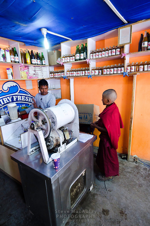 Young Buddhist monk wearing red robes, buying ice cream at shop in Leh, Ladakh, India.