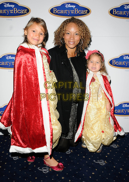 "ANGELA GRIFFIN & CHILDREN MELLISSA & TALLULAH.At Disney's ""Beauty And The Beast"" gala screening, Cafe de Paris, London, England, UK, September 26th 2010..full length family daughters black coat half kneeling down dressed up belle costume .CAP/CAN.©Can Nguyen/Capital Pictures."