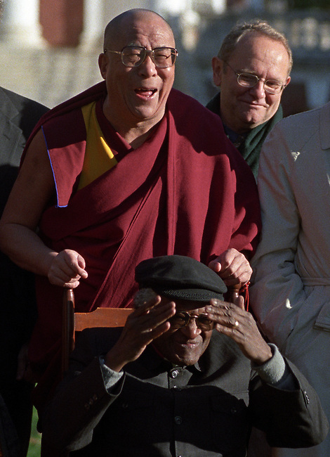 Bishop Desmond Tutu reacts as the Dalai Lama pulls on his hat during a group photo of Nobel Peace Laureates at the University of Virginia in Charlottesville in November of 1998.