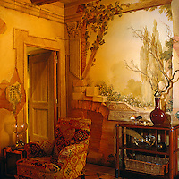 The walls of this sitting room are painted with a trompe l'oeil scene by Renzo Mongiardino which depicts a garden and crumbling architecture