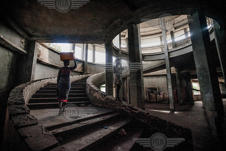 A woman carries a water vessel up the circular staircase in what was the lobby in the former Grand Hotel building. Once a luxury destination for the wealthy and the continent's biggest hotel, the building is now a concrete shell and home to about 6,000 squatters. Those unable to occupy one of the rooms sleep in the corridors, basements and even on the roof of the building.