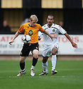 Simon Russell of Cambridge United holds off Paul Bignot of Newport during the Blue Square Bet Premier match between Cambridge United and Newport County at the Abbey Stadium, Cambridge  on 25th September, 2010.© Kevin Coleman