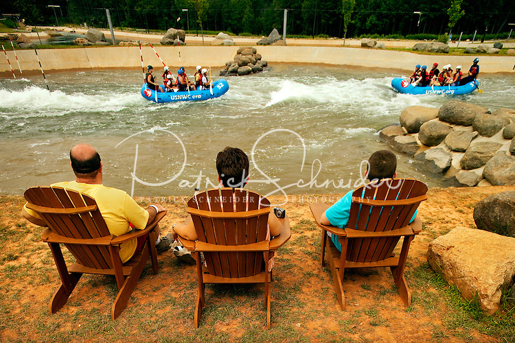 Visitors to the US National Whitewater Center (USNWC) watch river rafting participants navigate the center's manmade white water rapids courses. The USNWC's facilities offer multiple high-adventure outdoor sports, including ropes courses, zip line courses, rafting, canoeing, kayaking, hiking, biking, running and more. The center opened to the public in 2006.
