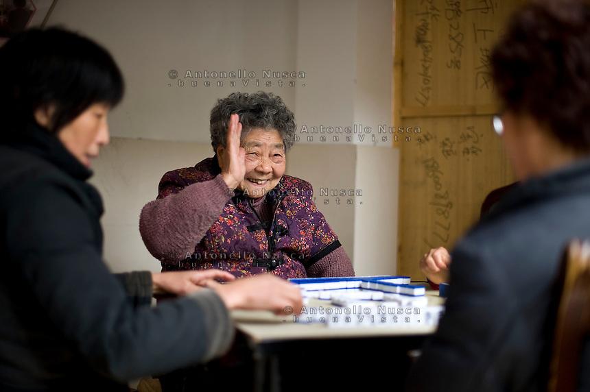 Una anziana signora saluta mentre gioca con le sue amiche in un condominio di Hangzhou.<br /> Greetings from Hangzhou