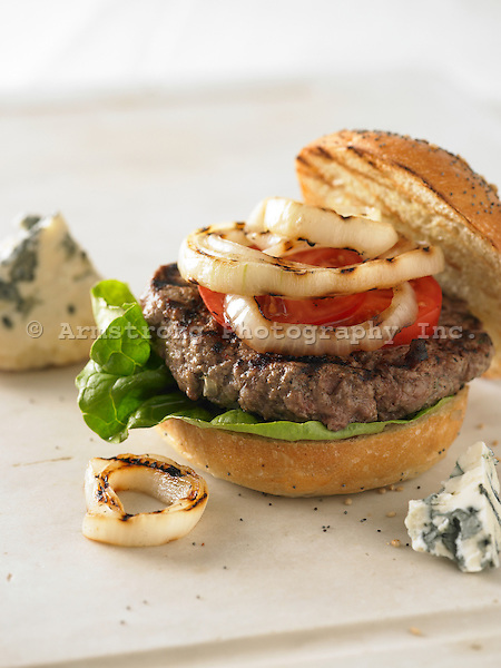 Gourmet hamburger with lettuce, tomato, and grilled onions. On grilled kaiser roll, pictured with chunks of blue cheese.