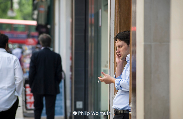 A man standing in a doorway using a mobile phone, Oxford Street, London.