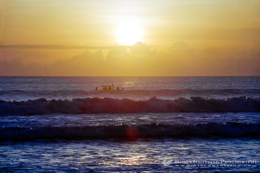 Bali, Badung, Kuta. Kuta is located on the west coast, and the sunsets here are world class. Small boat surfing the waves.
